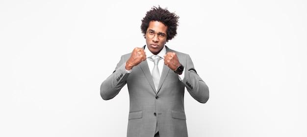 Zwarte afrozakenman die zelfverzekerd, boos, sterk en agressief kijkt, met vuisten klaar om in bokspositie te vechten