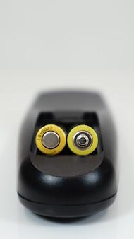 Zwarte afstandsbediening met gele aaa-batterijen op een witte achtergrond. vervanging van de batterij, reserveonderdelen. afstandsbediening batterijcompartiment close-up. verticale fotografie.
