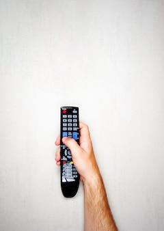 Zwarte afstandsbediening van de tv in een mannelijke hand op een lichtgrijze achtergrond, bovenaanzicht