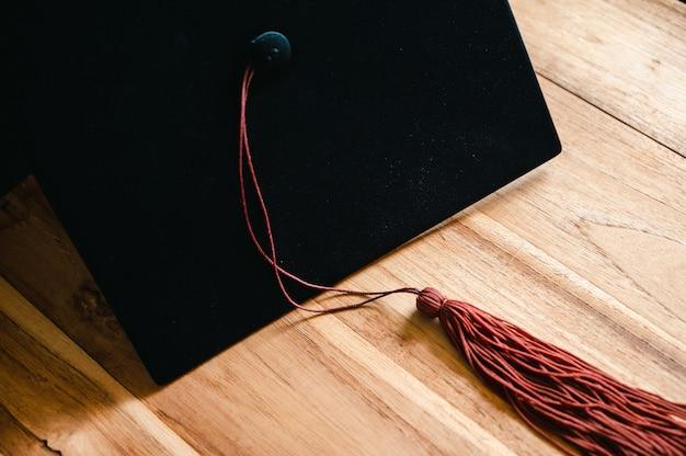 Zwarte afstudeerpet en bruine kwast op houten tafel