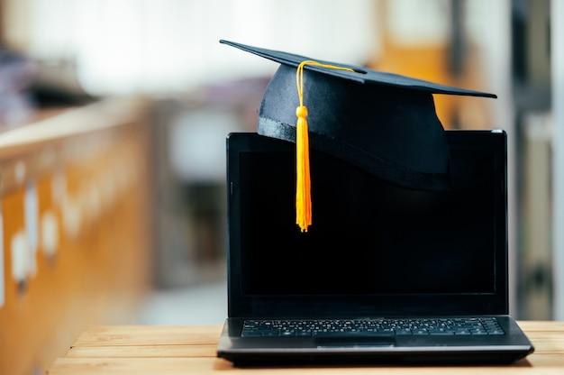 Zwarte afstudeerpet met gele kwastjes op laptop