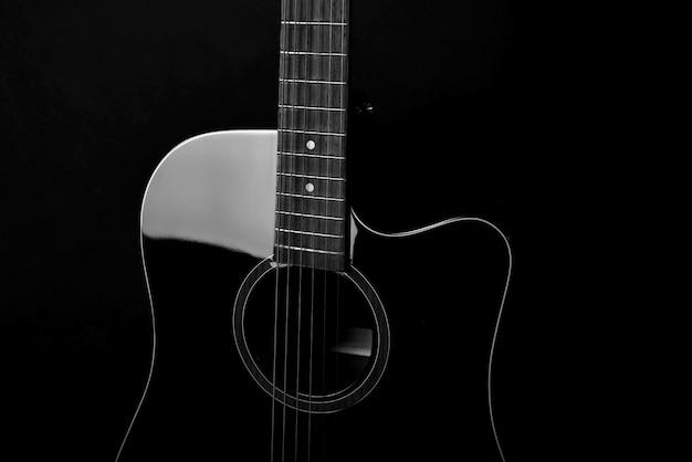 Zwarte akoestische gitaar op zwarte achtergrond, muziekinstrument voor hobby.