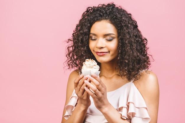 Zwarte amerikaanse afrikaanse gelukkige vrouw met krullend afro haarstijl die een puinhoop maken die een groot buitensporig dessert eten over roze achtergrond. cupcake eten.