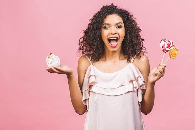 Zwarte amerikaanse afrikaanse gelukkige vrouw met krullend afro haarstijl die een puinhoop maken die een groot buitensporig dessert eten over roze achtergrond. cupcakes en snoep eten.