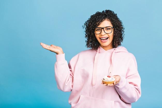 Zwarte amerikaanse afrikaanse gelukkige vrouw met krullend afro haarstijl die een puinhoop maken die een reusachtig buitensporig dessert eten over blauwe achtergrond. cupcake eten. wijzende vinger.