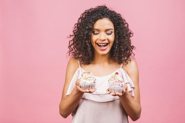 Zwarte amerikaanse afrikaanse gelukkige vrouw met krullend afro-kapsel die een puinhoop maakt die een enorm buitensporig dessert eet