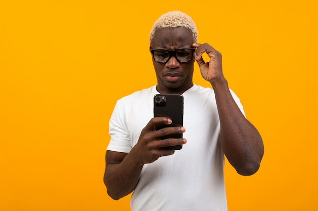 Zwarte amerikaanse man kijkt verrast op de telefoon op een gele achtergrond
