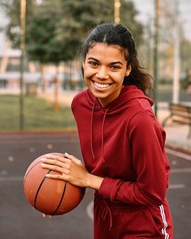 Zwarte amerikaanse vrouw die een basketbal houdt