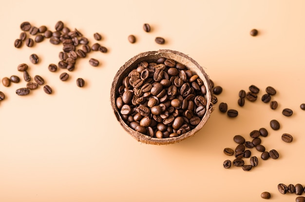 Zwarte arabica koffiebonen op een lichtoranje achtergrond