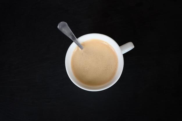 Zwarte aromakoffie in de witte kop met de lepel in bovenaanzicht op zwarte ondergrond