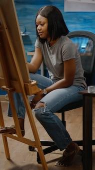 Zwarte artistieke persoon die meesterwerk van vaas op tafel in kunstwerkruimte ontwerpt. afro-amerikaanse jonge vrouw die moderne tekening maakt voor professioneel kunstproject. volwassen met creativiteit