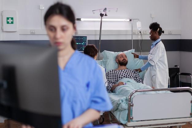 Zwarte arts die gehospitaliseerde zieke man controleert die ziektesymptomen controleert tijdens herstelafspraak...