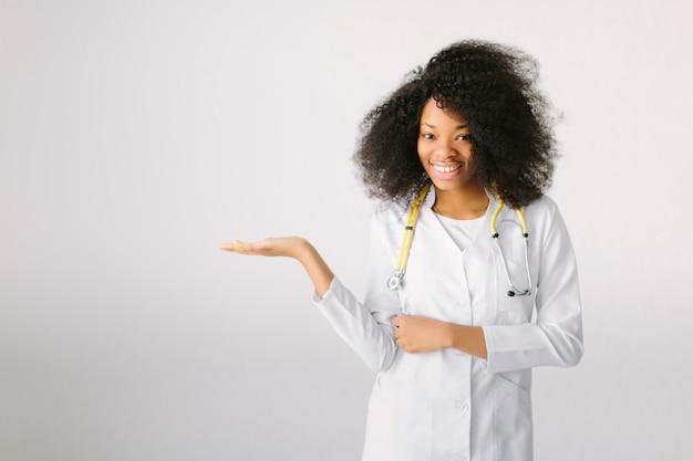 Zwarte arts die stethoscoop en laboratoriumlaag op wit geïsoleerde achtergrond draagt, die iets over haar hand toont
