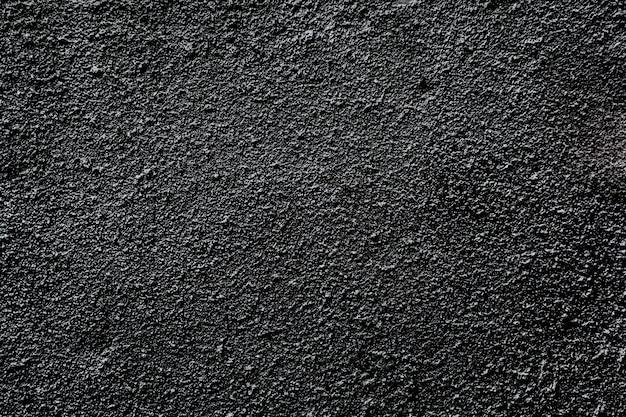 Zwarte asfalt korrelige muur