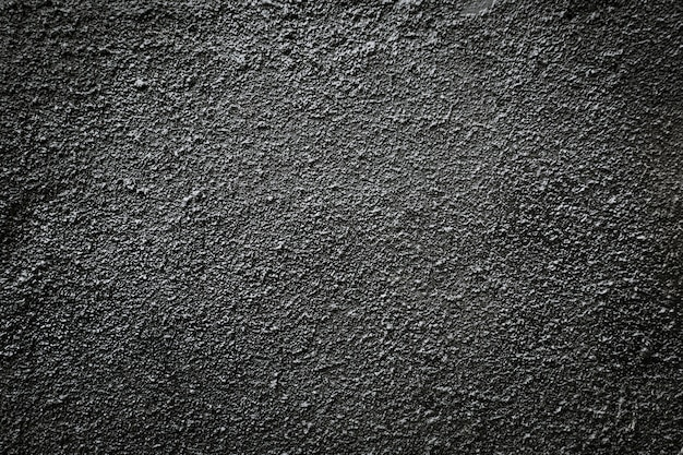 Zwarte asfalt korrelige muur.