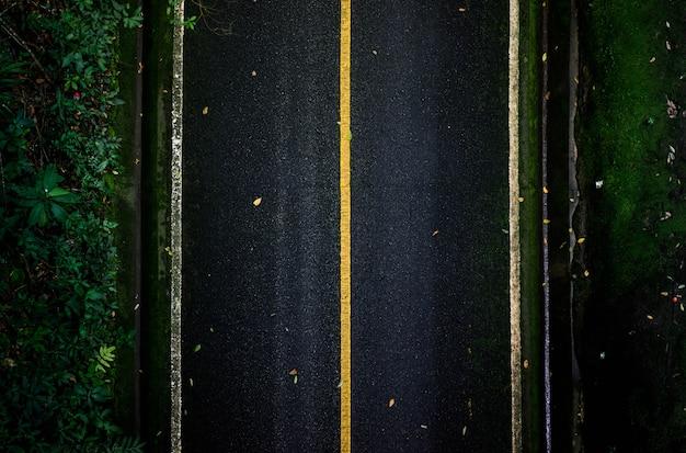 Zwarte asfaltweg die van bovenaanzicht eruit ziet met rechte lijnen