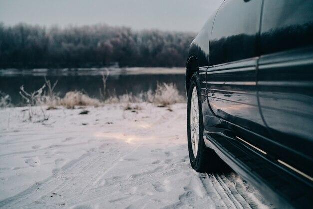 Zwarte auto dichtbij de rivier op een besneeuwde weg en bos op de achtergrond