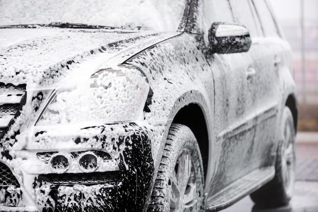 Zwarte auto in de zeep die zich openlucht bevindt. vooraanzicht