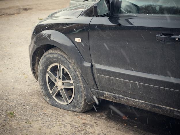 Zwarte auto met lek wiel onder de blote hemel.
