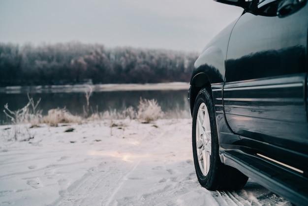 Zwarte auto natuur rivier winter reis reizen landschap.