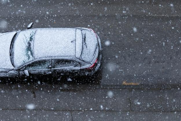 Zwarte auto op de weg onder de sneeuw in de lente in nieuw zagreb, kroatië