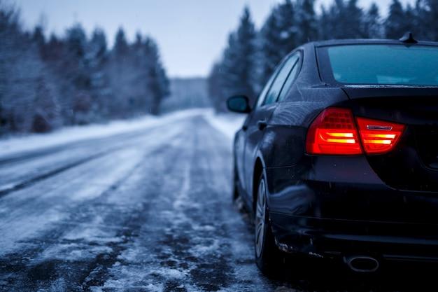 Zwarte auto op een bevroren weg omgeven door bomen bedekt met sneeuw