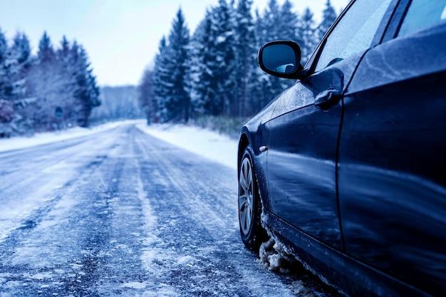 Zwarte auto op een bevroren weg omringd door bomen bedekt met sneeuw