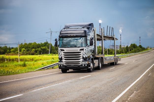 Zwarte autotransporter op een weg met elektriciteitscentrale op de achtergrond