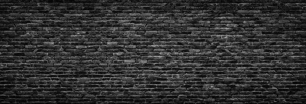 Zwarte bakstenen muur achtergrond. metselwerk textuur somber, panoramisch uitzicht