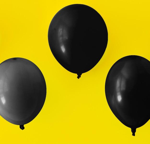 Zwarte ballonnen op gele achtergrond