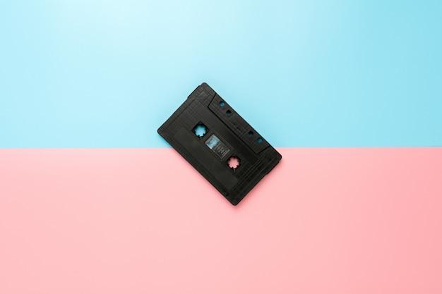 Zwarte bandcassette op blauwe en roze achtergrond.
