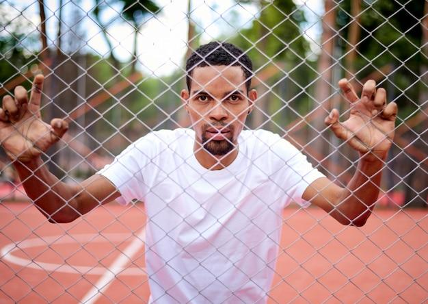 Zwarte basketbalspeler die het hek van de kettingslink met handen houdt