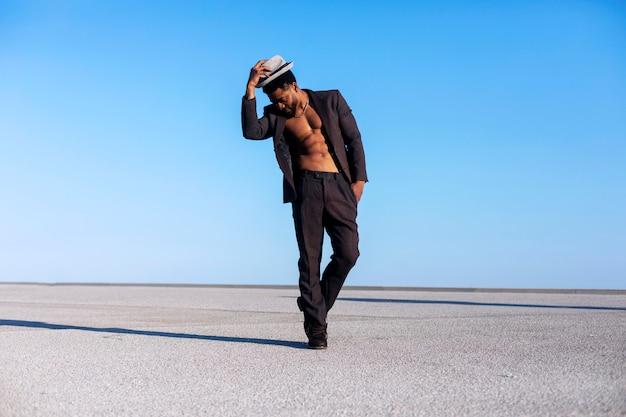 Zwarte bebaarde m met een hoed tijdens het dansen en genieten tegen blauwe hemel in een zonnige dag