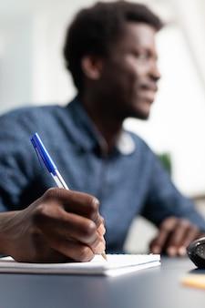 Zwarte bedrijfsstudent die aantekeningen maakt op notebook met behulp van computer op afstand werken vanuit huis en o...