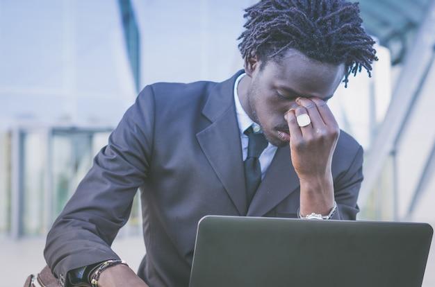 Zwarte beklemtoonde zakenman die zijn laptop met behulp van
