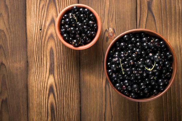 Zwarte bes op houten tafel met blad takje