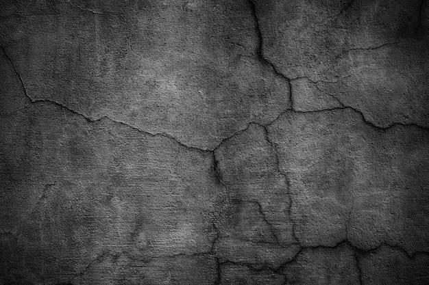Zwarte betonnen muur bedekt met scheuren.
