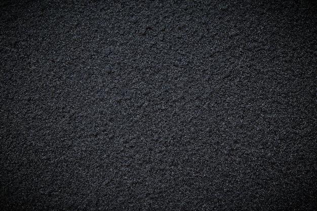 Zwarte betonwegmuur als achtergrond of textuur