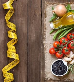 Zwarte biologische rijst, olijfolie, rauwe groenten en kruiden ton houten tafelblad weergave met kopie ruimte
