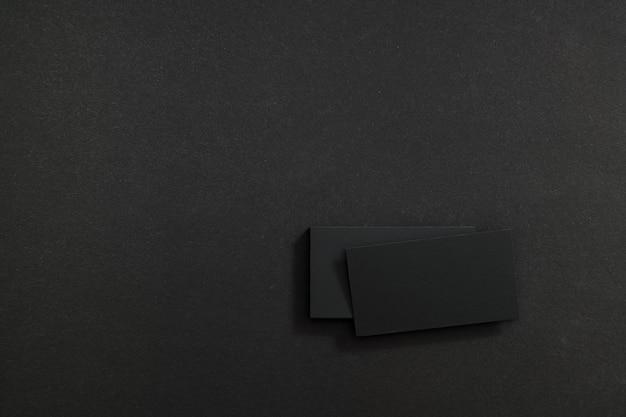Zwarte blanco visitekaartjes op een zwarte ondergrond.