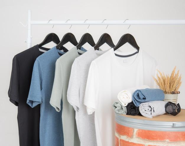 Zwarte, blauwe, grijze en witte t-shirts op hangers op een grijze achtergrond