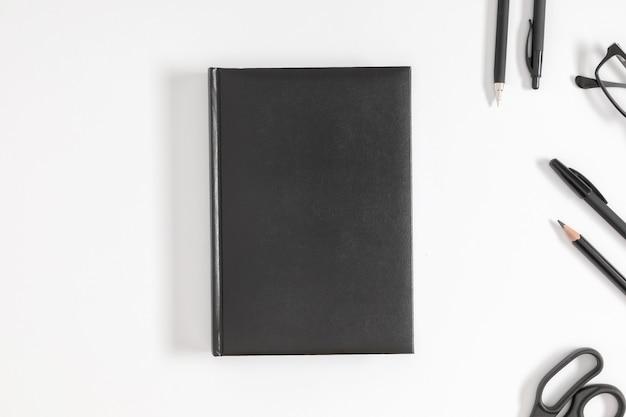 Zwarte boekomslag mock up en briefpapier op witte achtergrond