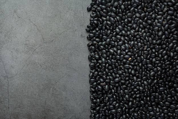 Zwarte bonen en kale cementachtergrond