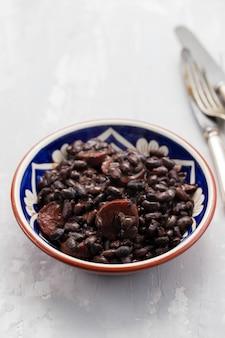 Zwarte bonen met rookworst in ceramische schotel