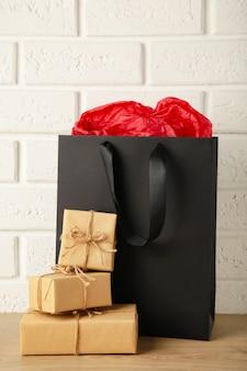 Zwarte boodschappentas met cadeau op lichte achtergrond. zwarte vrijdag. bovenaanzicht