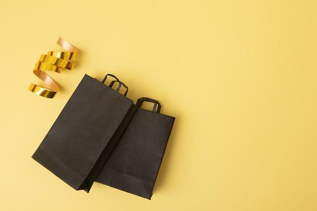 Zwarte boodschappentassen in black friday-verkoop plat tegen een gele achtergrond met feestelijke slinger