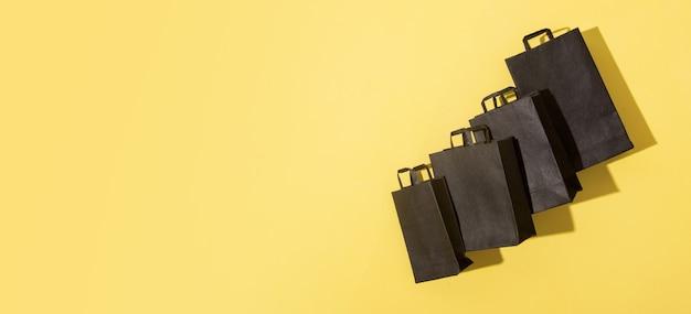 Zwarte boodschappentassen op zwarte vrijdag verkoop gele achtergrond met kopie ruimte in banner-formaat
