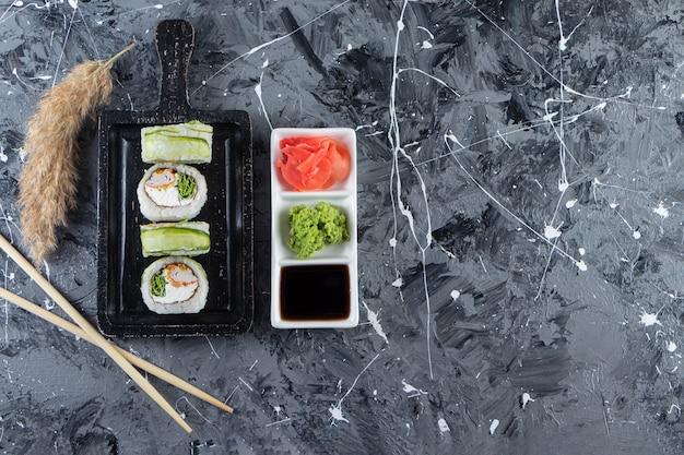 Zwarte bord met groene drakensushi rolt op marmeren achtergrond.