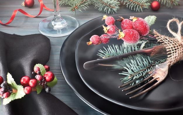 Zwarte borden en bestek met kerstversiering op donker, close-up