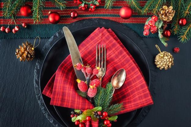 Zwarte borden en vintage bestek met kerstdecoraties in groen en rood